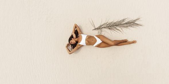 Top aerial drone view of woman in swimsuit relaxing and sunbathing on beach Near The Ocean. Attractive brunette girl in white bikini laying on a sandy coast with palm leaf. Gorgeous tanned mixed race Asian Caucasian model on vacation. Summer holiday fashion concept