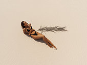 istock Top Aerial Drone View of Woman in Swimsuit Bikini Relaxing and Sunbathing on Beach 1253402104