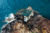 Top aerial view of turquoise Atlantic ocean water waves crashing on rocks on the Portuguese Madera island seashore.