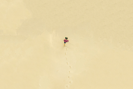 top aerial view of young lonely man walk in desert on the sand texture. lost concept