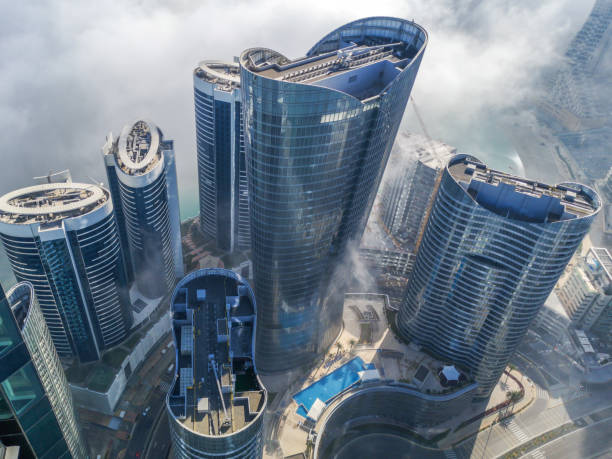 top aerial view shot of skyscrapers in the city with fog clouds passing by - abu dhabi al reem island towers - abu dhabi стоковые фото и изображения