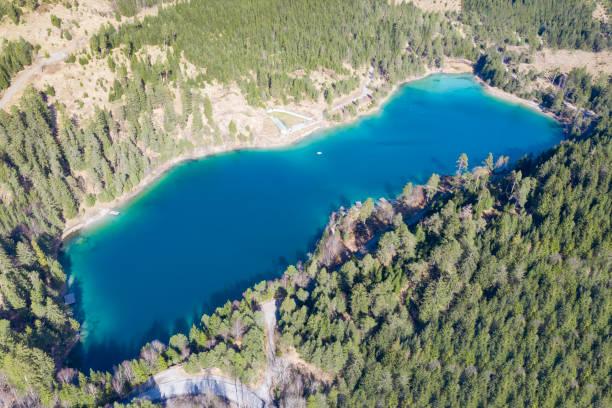 Top Luftaufnahme zum frischen blauen See urisee im grünen österreichischen Alpenwald im Frühling – Foto