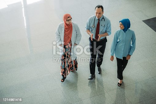 Top angle view of asian doctors and nurses having discussion when waliking at the lobby hospital