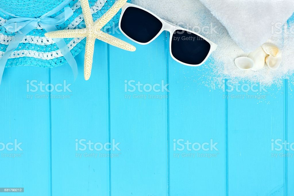 Top border of beach items and seashells on blue wood stock photo