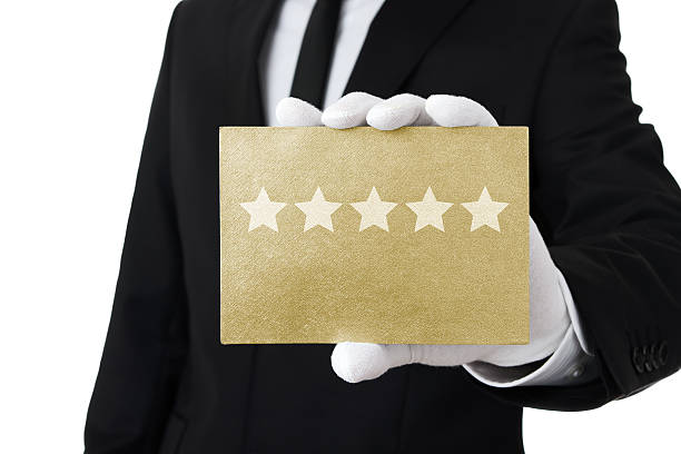 Top class service Human hand holding gold card with five stars on it first class stock pictures, royalty-free photos & images