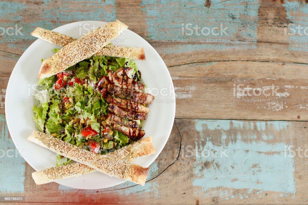 Close-up van top over een plaat met salade op een rustieke achtergrond - Royalty-free Avondmaaltijd Stockfoto