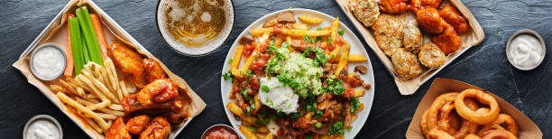 top down photo of carne asada fries and buffalo chicklen wings stock photo
