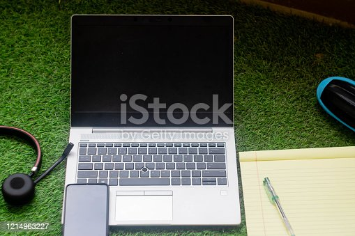 Top down shot of a laptop with headphone, mobile phone, notepad with pen and a wireless speaker for working remotely or from home. Digital nomad freelancers connect across the world and work or attend tele conferences