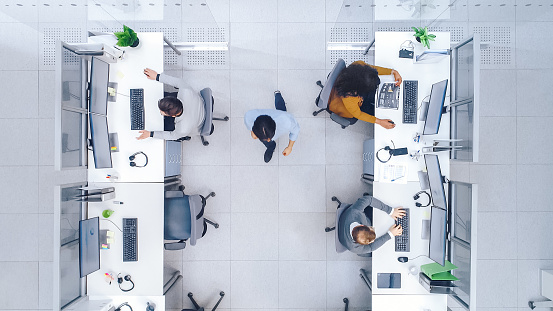 Top Down Shot of Big Busy Corporate Office with Two Rows off Businessmen and Businesswomen Working on Desktop Computers. Director is Walking Between Rows. Open Space Office with Businesspeople