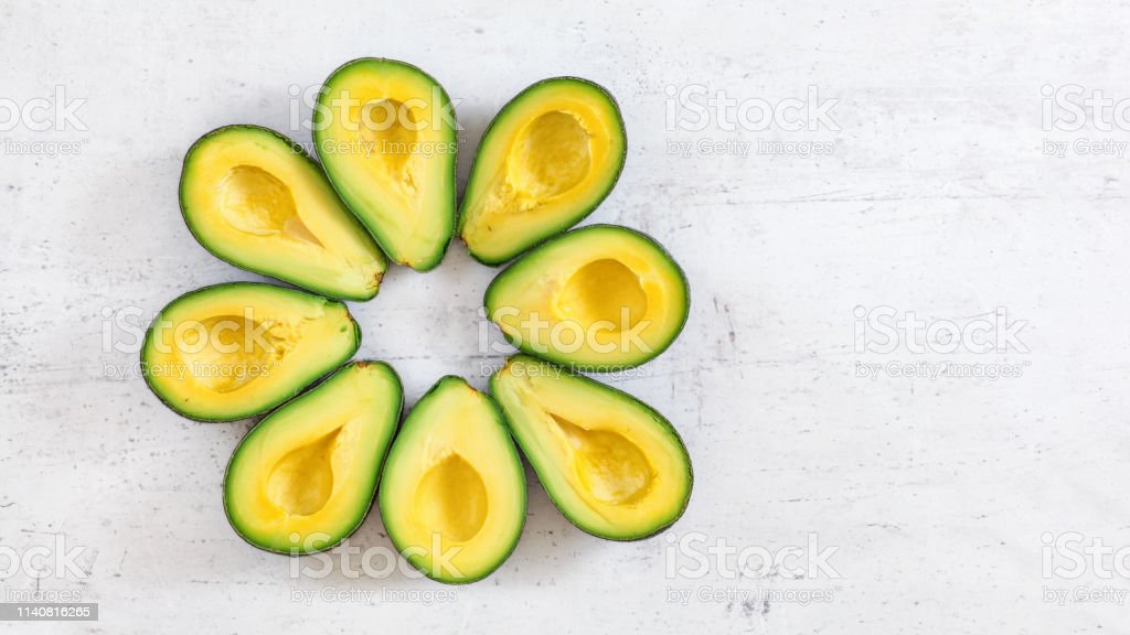 Top down view, 8 avocado halves arranged in circle on white board,...