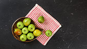 istock Top down view, green apples and pears in wooden carved bowl, red chequered tablecloth and black marble board under. 1089300542