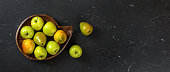 istock Top down view, green apples and pears in wooden carved bowl, red chequered tablecloth and black marble board under. 1136054716