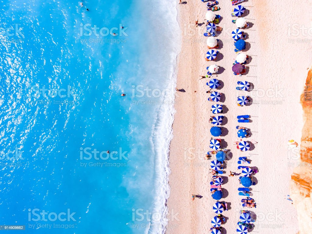 Top down view of a beach with tourists suntbeds and umbrellas with sand beach and clear blue water in Greece stock photo