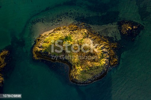 Aerial shot in the morning light of an island located in a fjord/firth in the west highlands of Scotland.