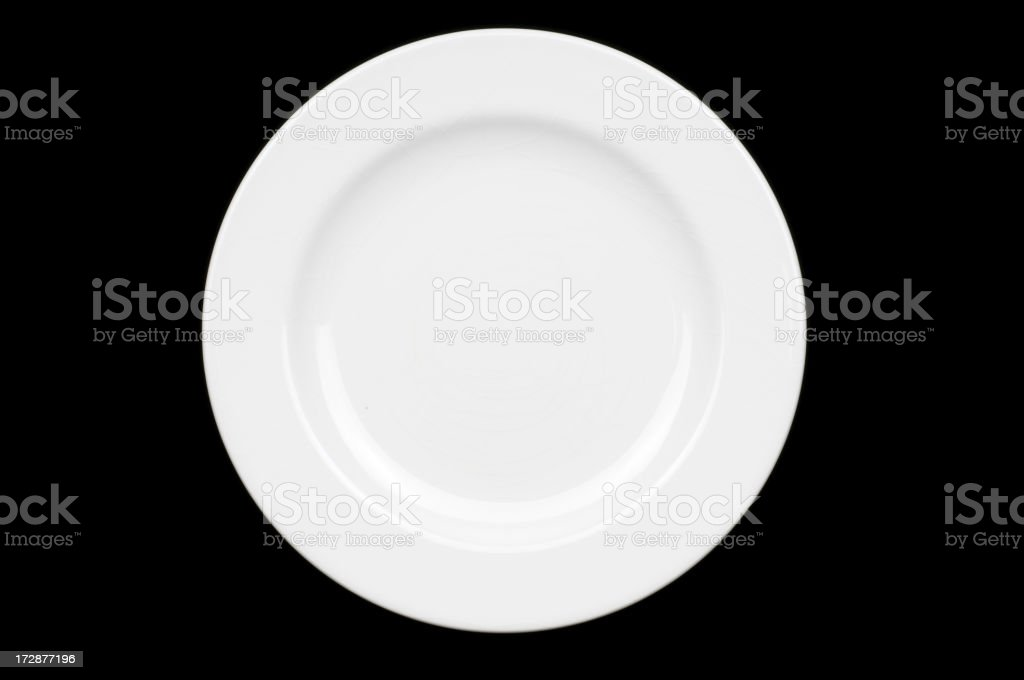 Top down view of empty white dinner plate on black surface royalty-free stock photo