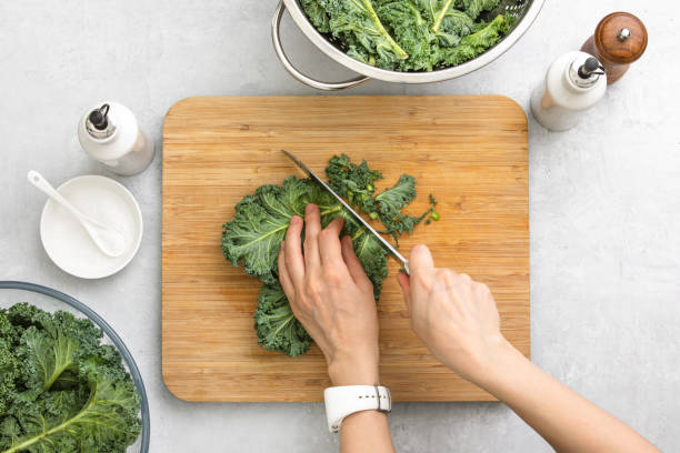 Top down view of fresh kale leaves cut on a cutting board Fresh kale leaves are cut by woman's hands on a cutting board, healthy or clean eating concept, overhead view image kale stock pictures, royalty-free photos & images