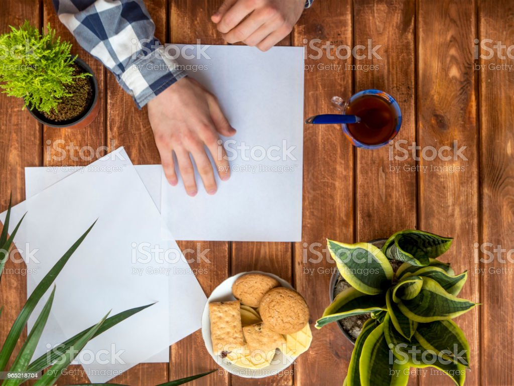 top down view of hands making paper origami on the table with flowers royalty-free stock photo