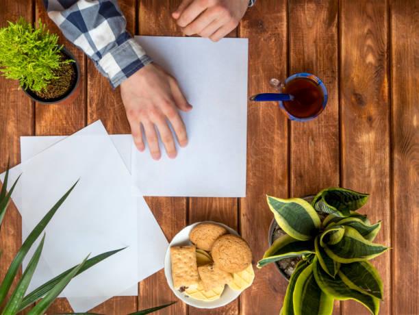 top-down-ansicht der hände machen origami papier auf den tisch mit blumen - origami anleitungen stock-fotos und bilder