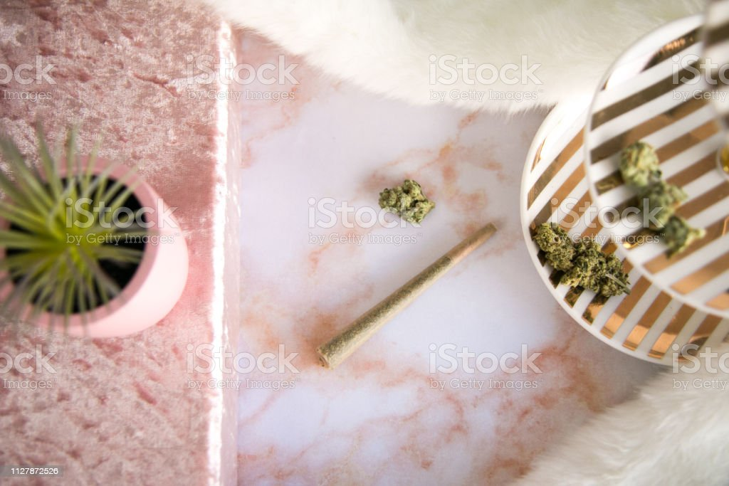 Top Down View of Marijuana Joint and Bud on Pink Marble Vanity Luxury Cannabis stock photo