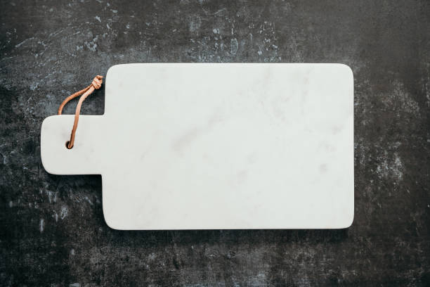 Top down view on an empty white marble cutting board. stock photo