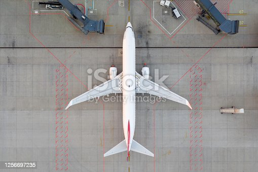 Top down view on comercial airplane docking in terminal in the parking lot of the airport apron. Modern airliner