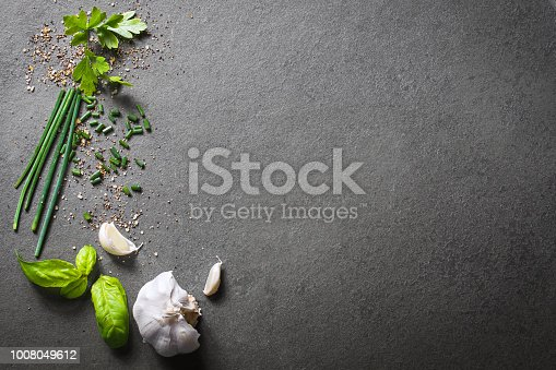 A Top Down View On Kitchen Ingredients Like Garlic, Basil, Spices And Herbs On Slate Stone, With Free Space In The Middle And Right Side