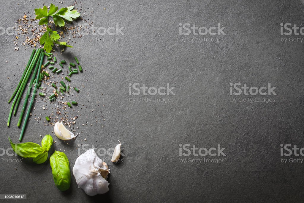Top Down View On Kitchen Ingredients Like Garlic, Basil, Spices And Herbs On Slate Stone, With Free Space In The Middle And Right Side stock photo