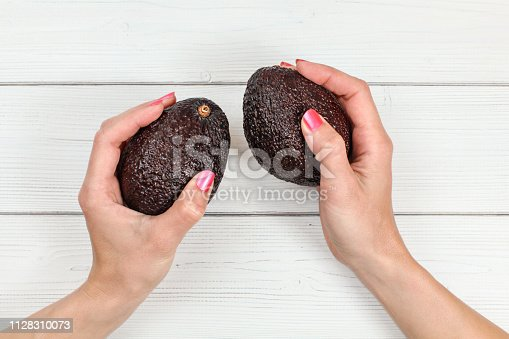 Top down view, woman hands with pink nails holding two whole dark ripe avocados over white boards desk.