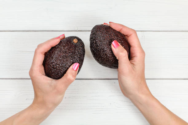 top down view, woman hands with pink nails holding two whole dark ripe avocados over white boards desk. - maturo foto e immagini stock