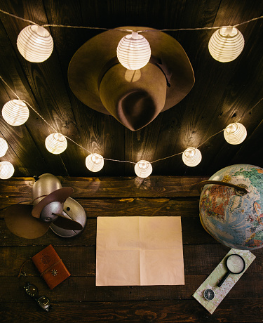 Overhead night view of traveler's desk while writing a letter, making a plan of a trip in remote, off grid wooden hut. Empty space for copy, room for text. Analog wild holiday vibe wanderlust concept. Dark vertical shot.