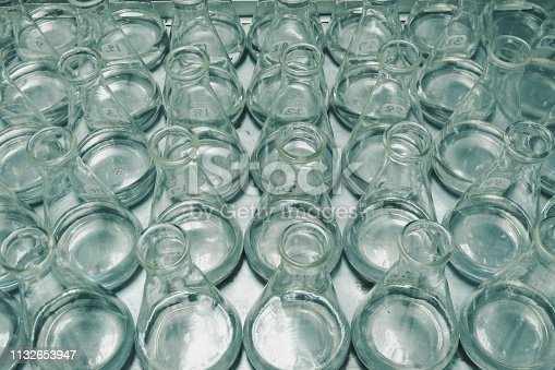 891126112istockphoto Top eye level view close-up of beaker science chemistry empty bottles or liquid put down on stainless tray at laboratory factory industrial or medical healthy care center. 1132653947