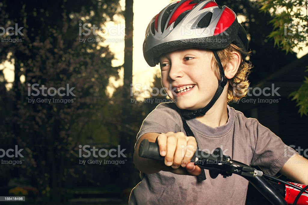 Top half of a smiling young boy riding a bike outside stock photo