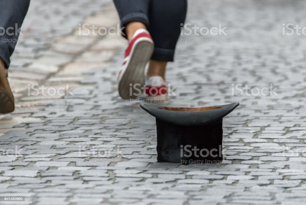 Top hat on cobblestone with people walking by stock photo