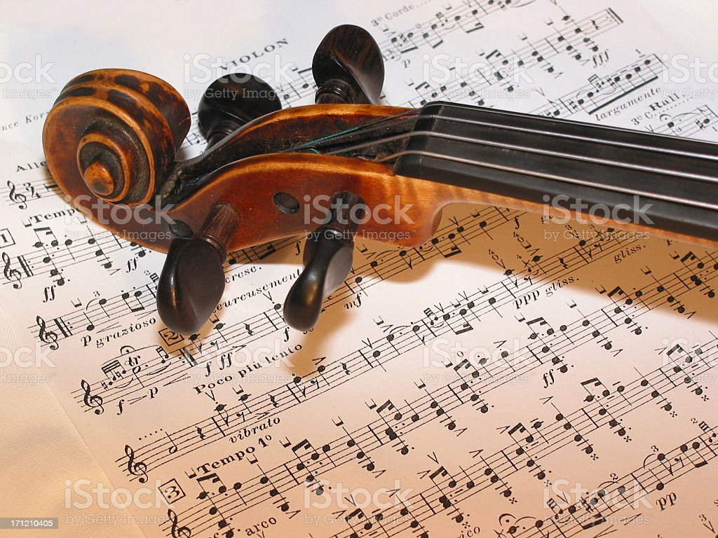 Top of a cello resting on sheet music royalty-free stock photo