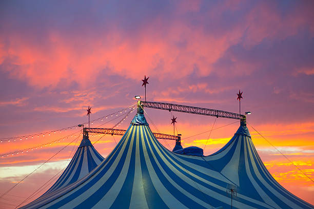 top of blue and white circus tent against a vivid sunset - circus stok fotoğraflar ve resimler