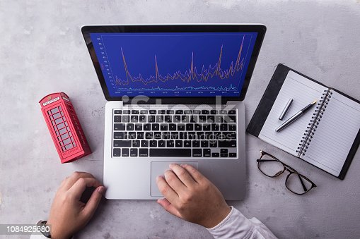 istock Top of businessman using laptop computer with stock chart market on screen. Working with financial graphs charts, using business software for data analysis and project management concept. 1084925580