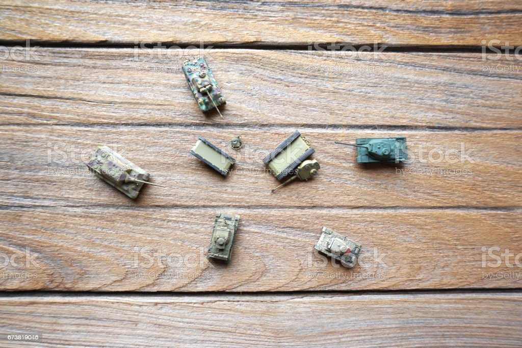 Top of old toy tanks on wooden background. stock photo