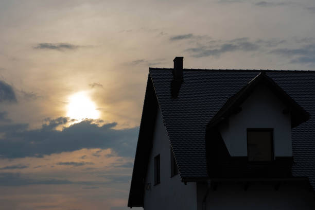 top of the house with a roof and a loft at sunset. stock photo