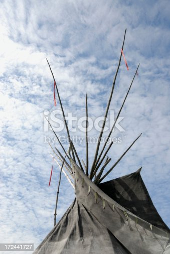 Top of a Native American Tipi against a blue sky filled with altostratus clouds.