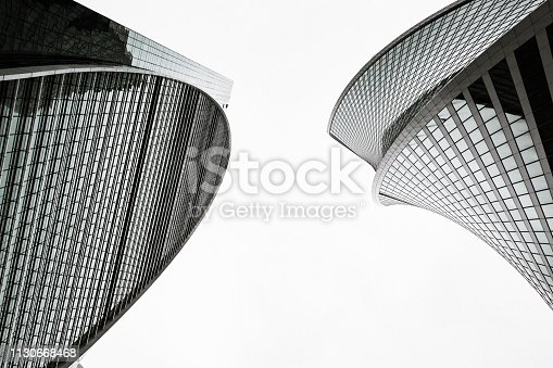 Skyscrapers with glass facades. Abstract modern buildings exterior, vintage stylized with grain. Bottom up view. Black and white.