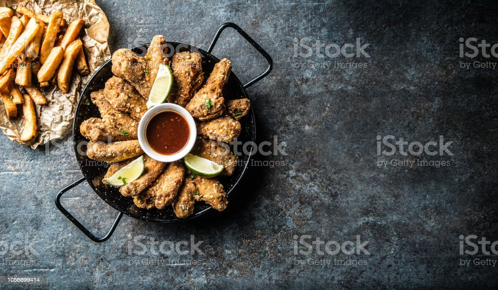 Top of view fried chicken wings chili sauce lime and potato fries. stock photo