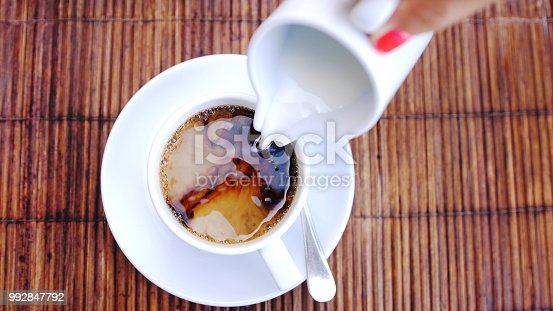 Top of view of pouring stream milk into a cup of espresso on wooden table.