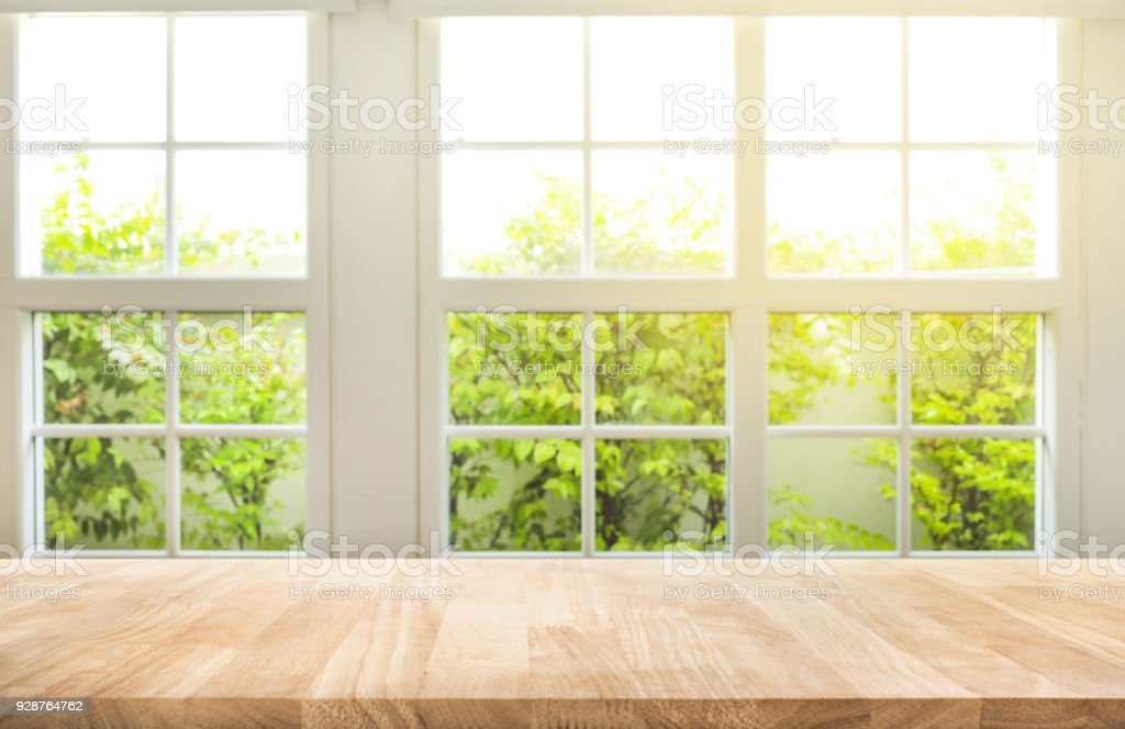 Top of wood table counter on blur window view garden background.