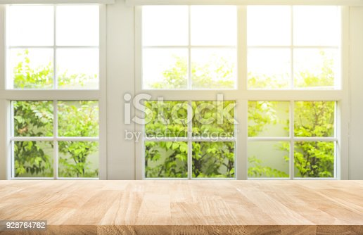 885452818istockphoto Top of wood table counter on blur window view garden background. 928764762