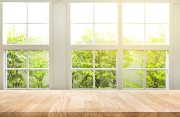 górna część drewnianego licznika stołu na tle ogrodu z widokiem na okno rozmycia. - okno zdjęcia i obrazy z banku zdjęć