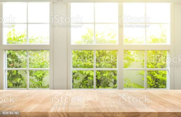 Top of wood table counter on blur window view garden background.For montage product display or design key visual layout