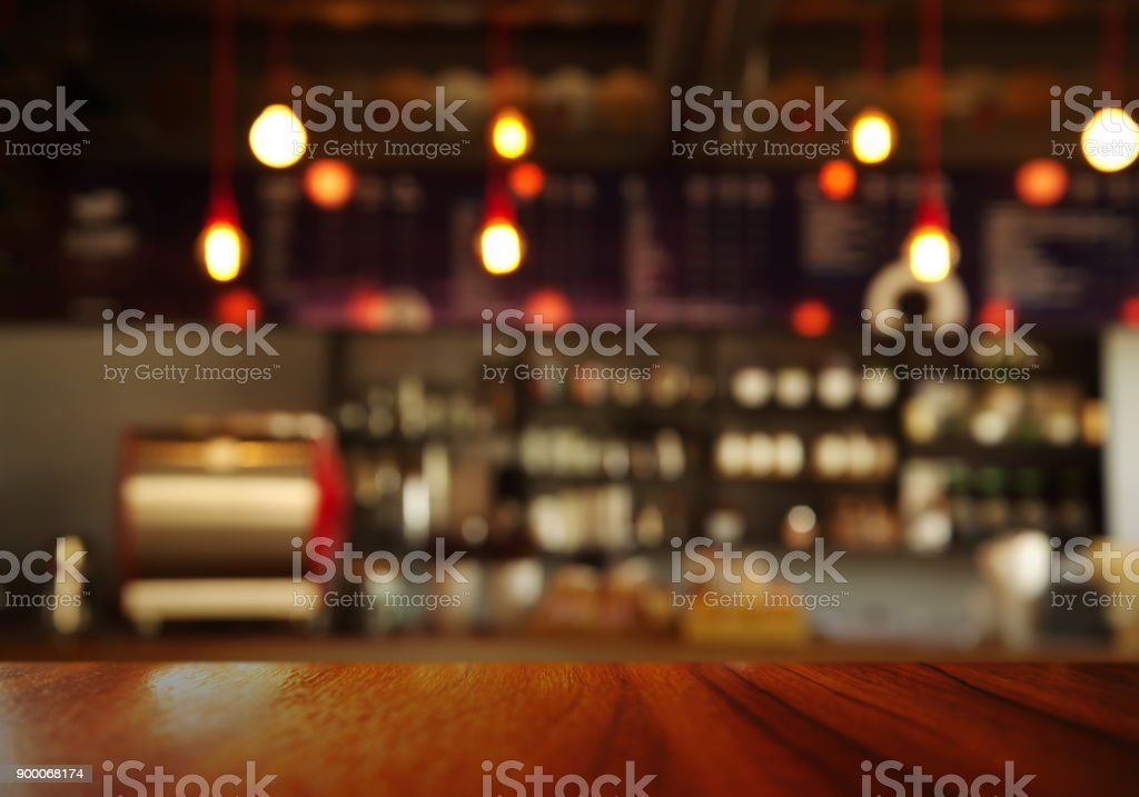 top of wood table with blur counter of coffee shop or cafe bar with lamp light background stock photo