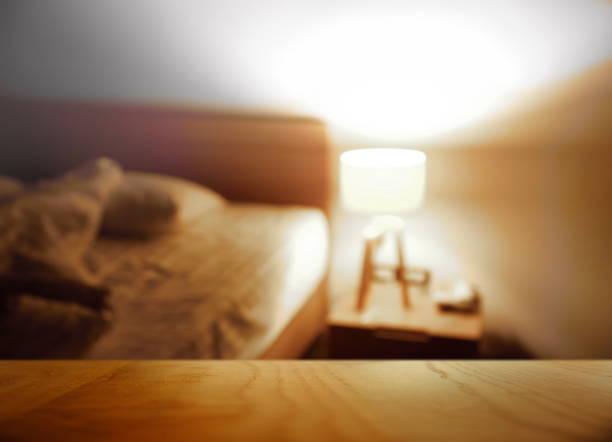 spitze der holztisch mit blur nacht schlafzimmer mit lampe haus innen hintergrund - nachttischleuchte stock-fotos und bilder