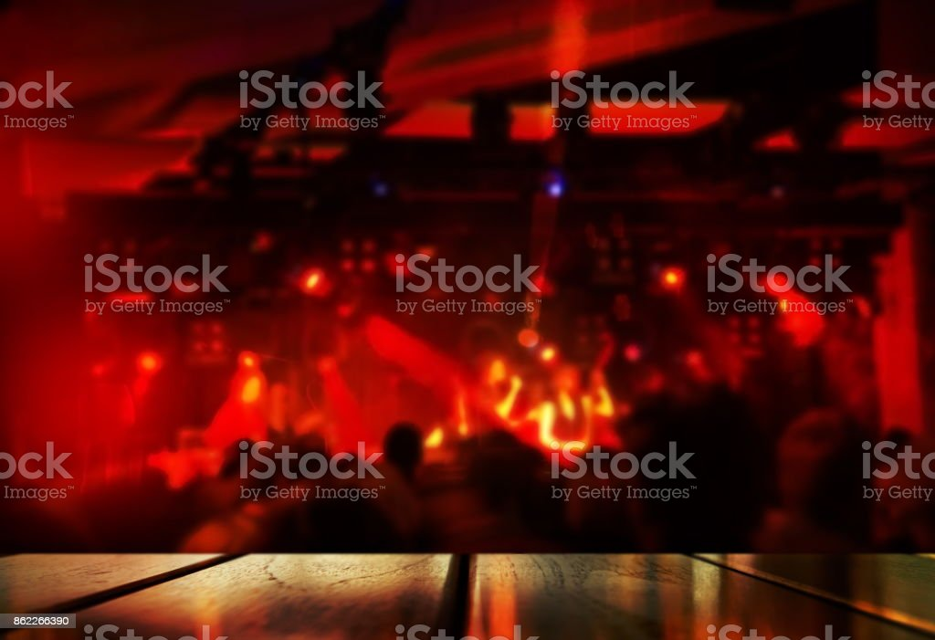 top of wood table with blur red light music performance party in bar or club at night background stock photo