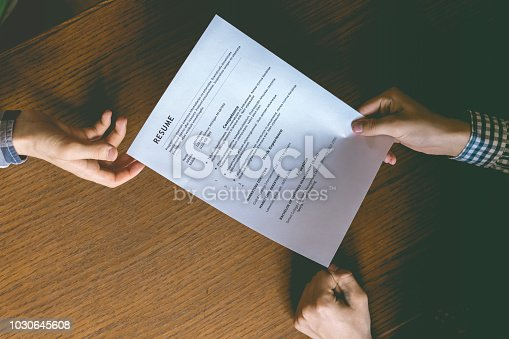 top overhead directly above view of employee hiring person and examine the resume on the office table